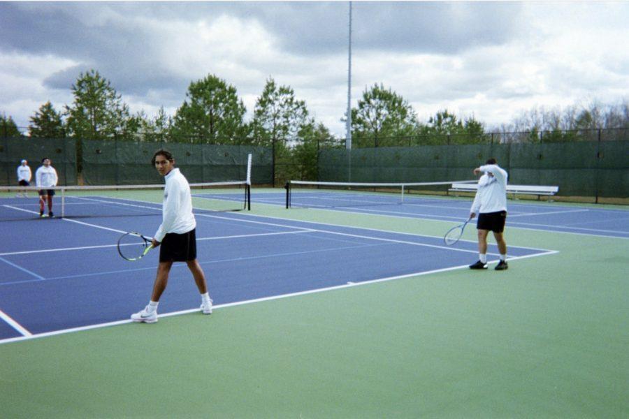Boys+tennis+team+practicing+serving.