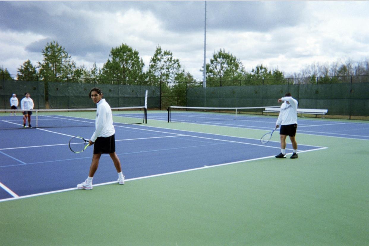 Boys tennis team practicing serving.